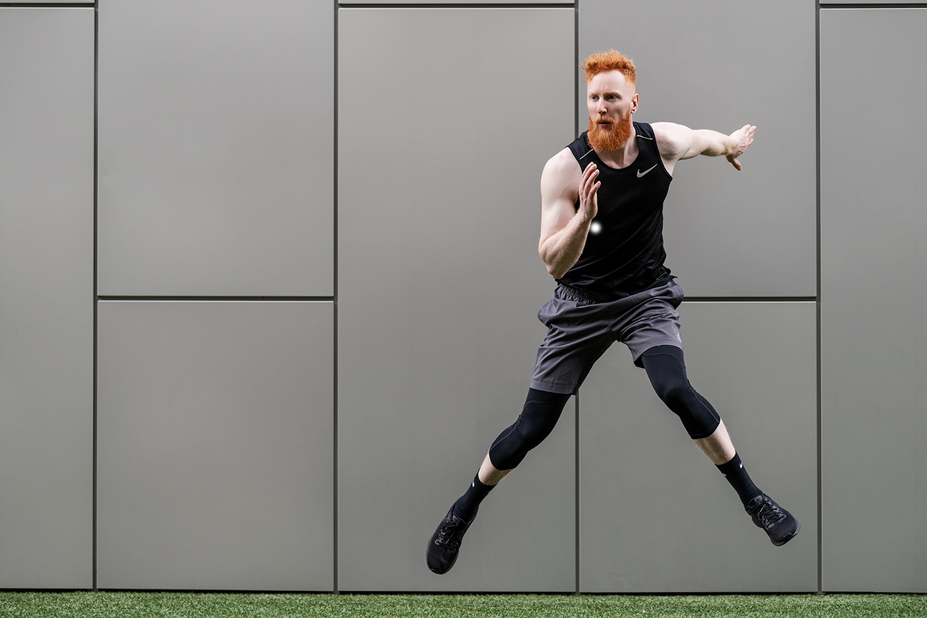 Jared jumping sideways in fitness shoot wearing black Nike compression pants and sleeveless Nike T-shirt