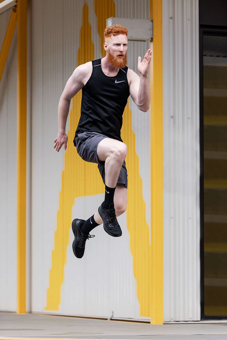 Jared redheaded fitness model jumping in black Nike gear
