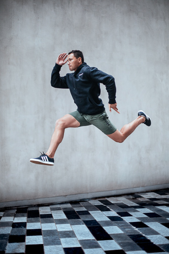 Jesse jumping in grey Nike shorts and Nike windbreaker
