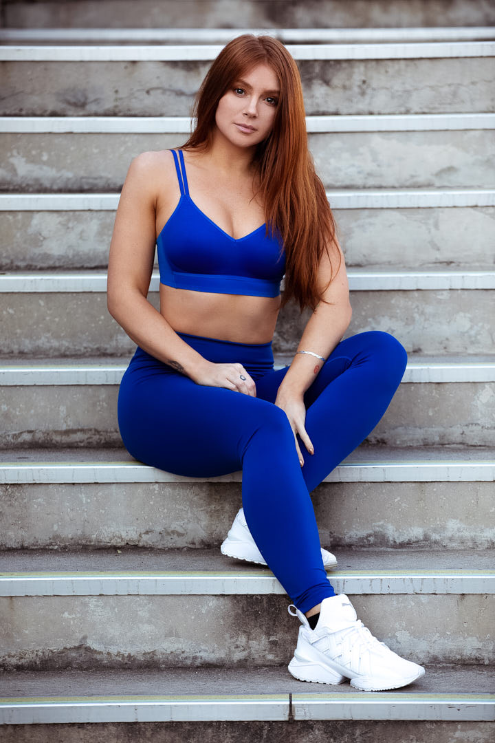 Jessica sitting on concrete steps in purple leggings and matching top