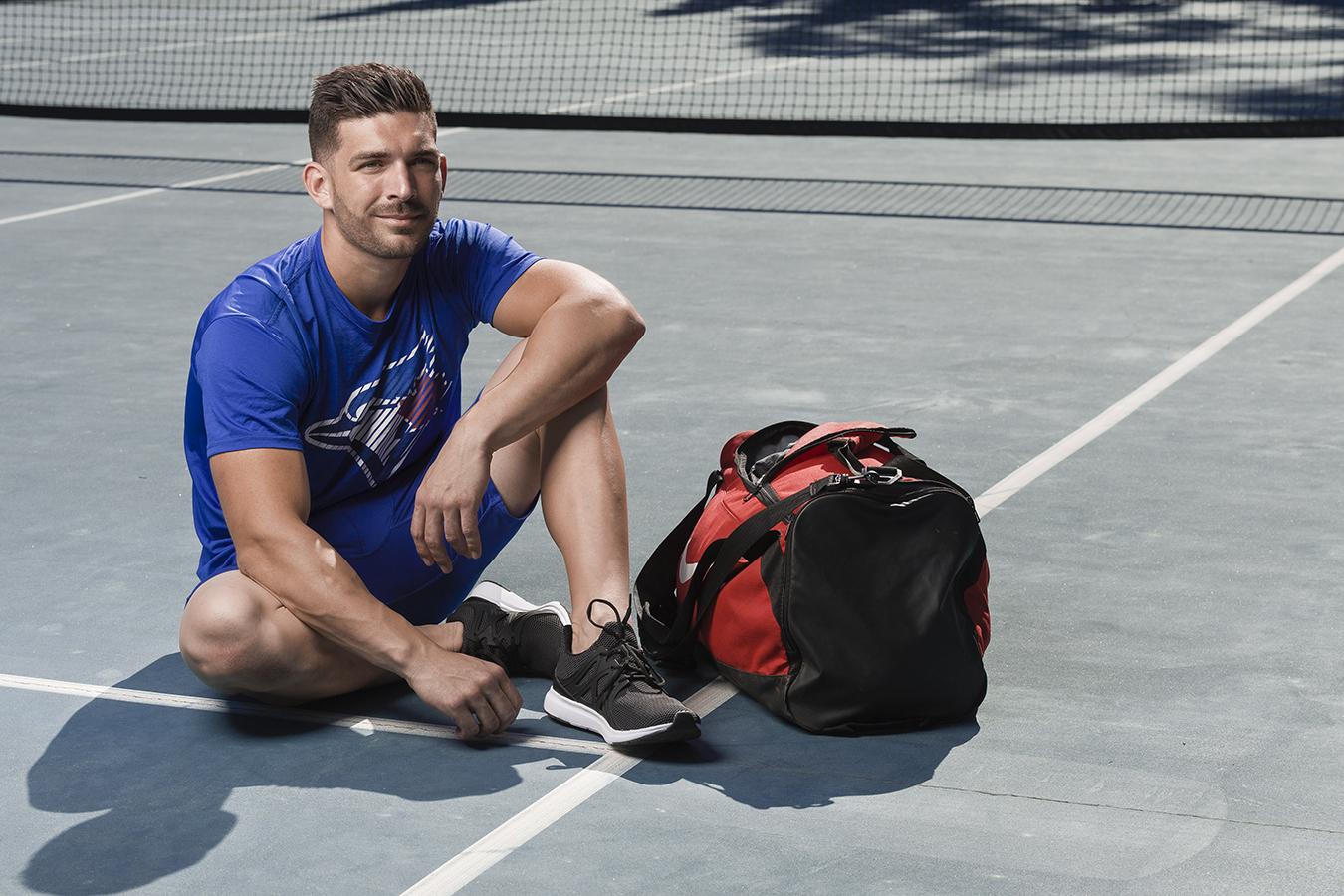 John seated on tennis court