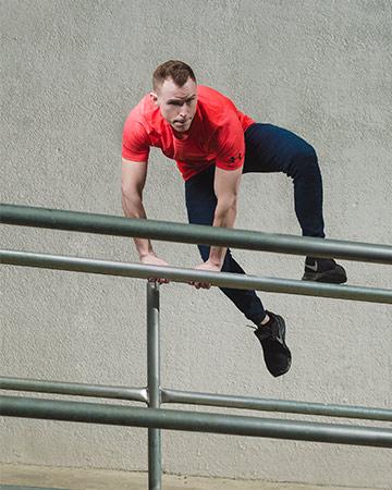 Jordan climbing over a metal banister