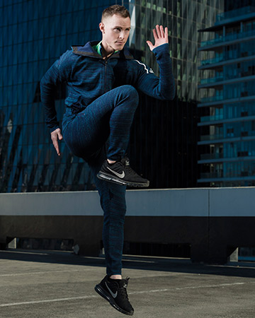 Jordan leaping as he runs on Melbourne rooftop