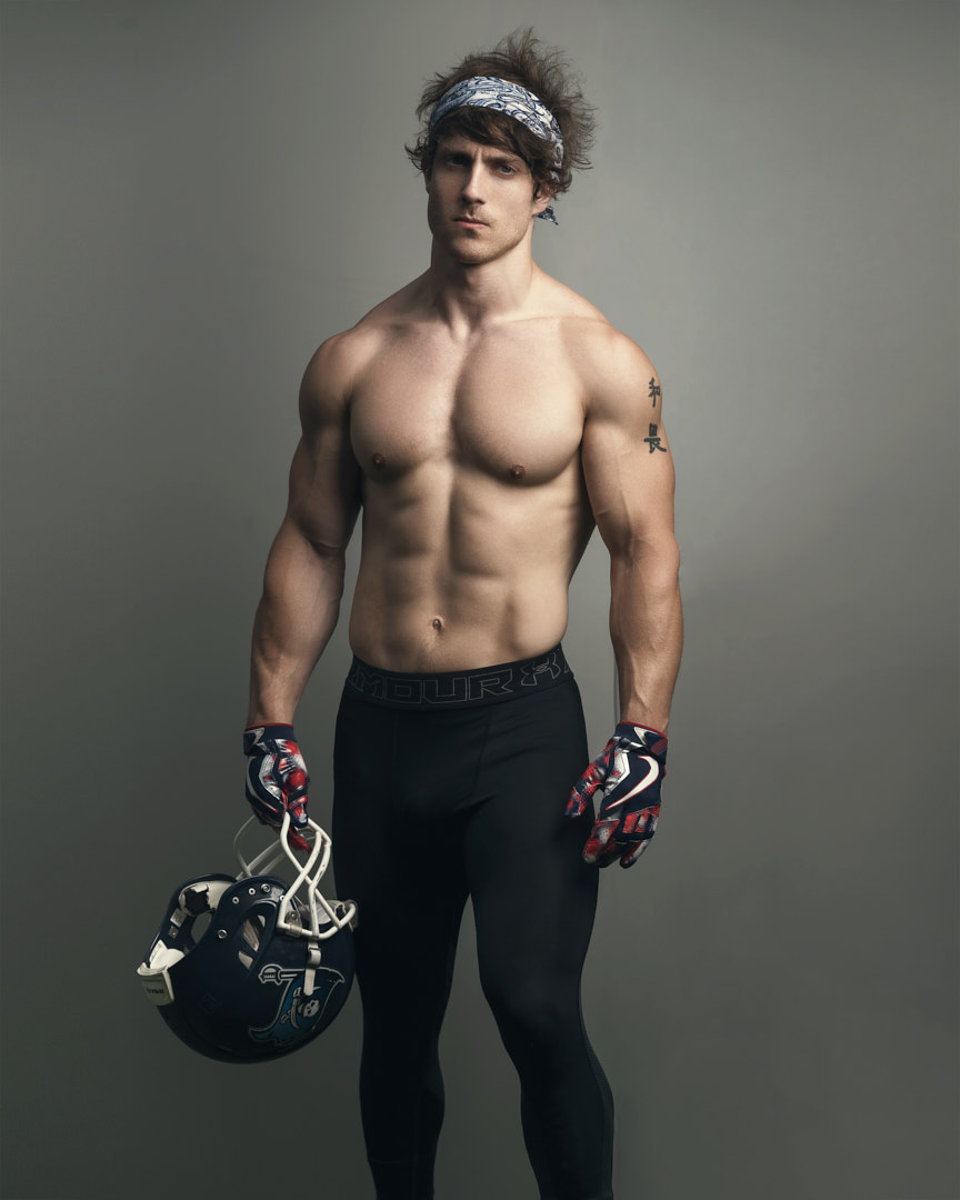 Justin Melbourne's male fitness model holding NFL helmet and wearing bandanna