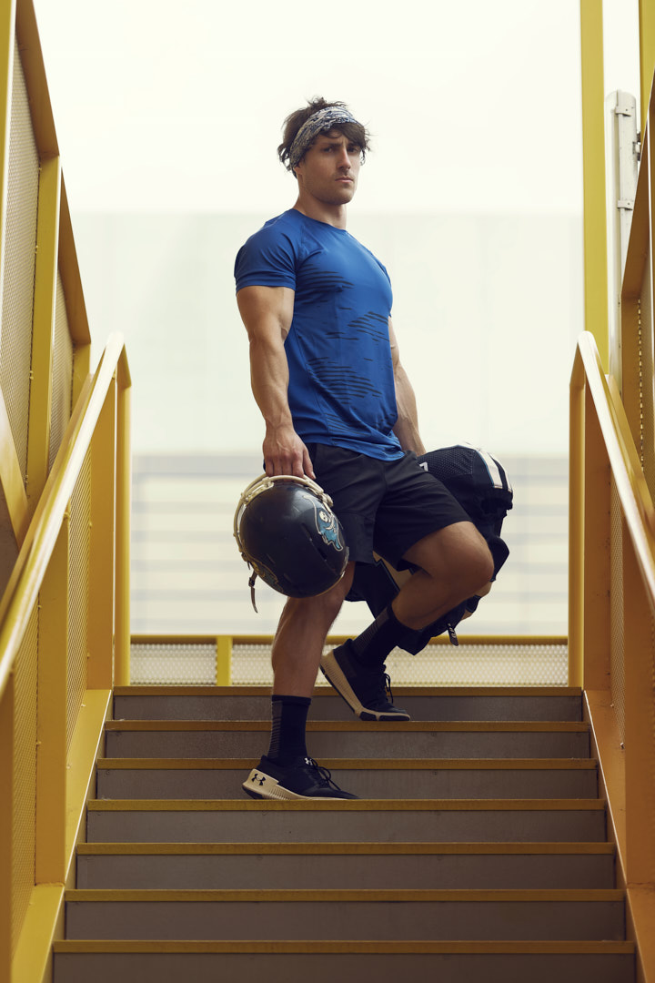 Justin holding NFL padding and helmet in stairwell