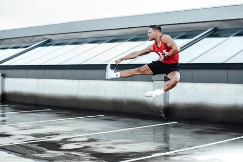 Kacper doing a high karate kick on rooftop carpark