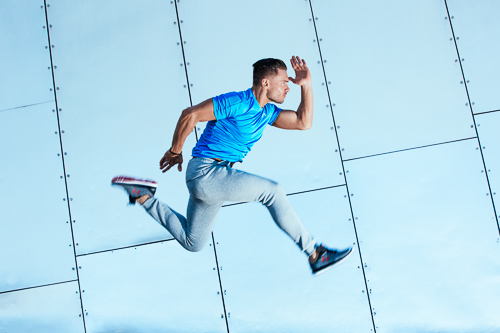 Kacper jumping in grey tracksuit bottoms an electric blue top