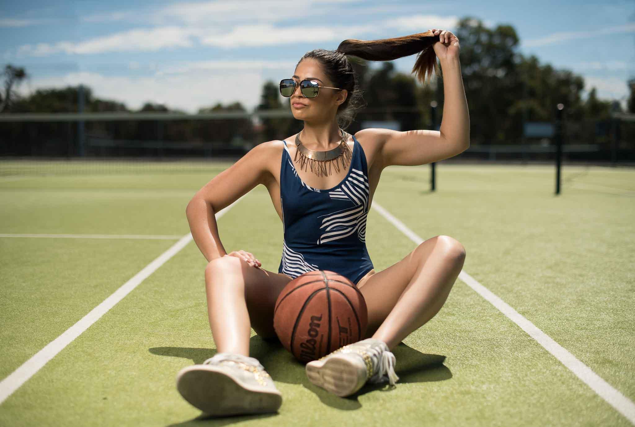 Karina Perth's female fitness model sitting on grass tennis court