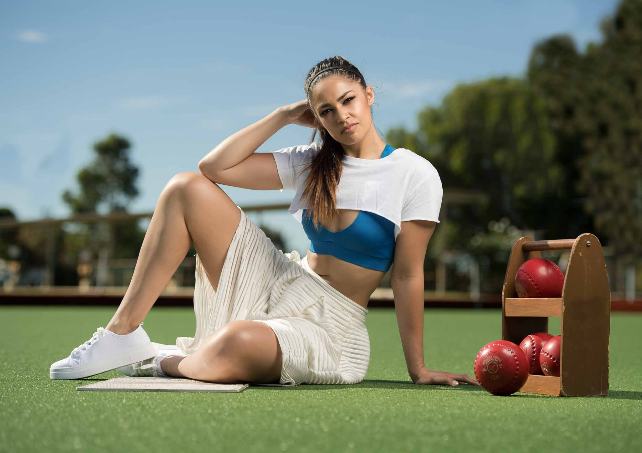Karina Perth's female fitness talent seated on lawn bowls green