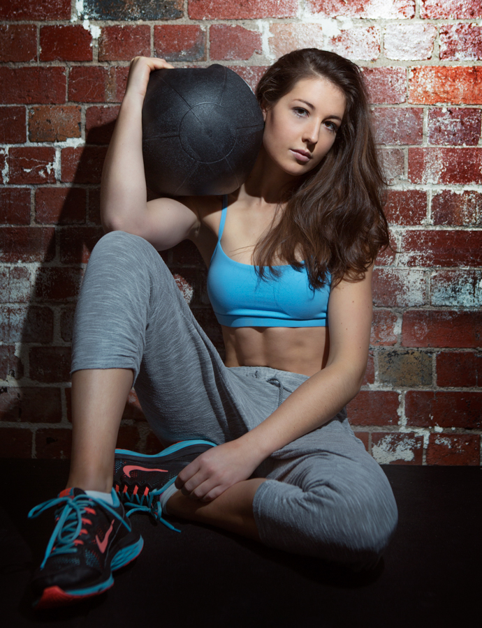 Kate seated holding medicine ball