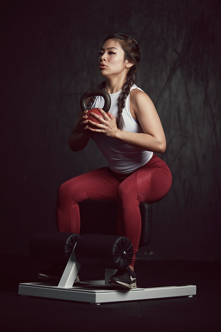 Kaylyn perform's squats holding Kettlebell
