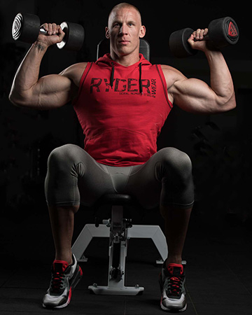 Keegan performing dumbbell shoulder press whilst wearing ryderwear sports gear