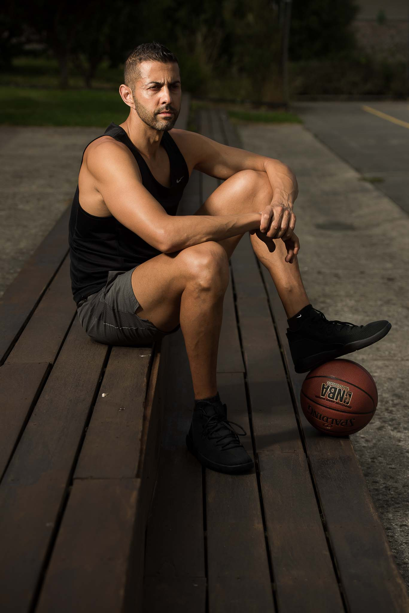 Keith Melbourne's personal trainer posing with his foot on a Basketball