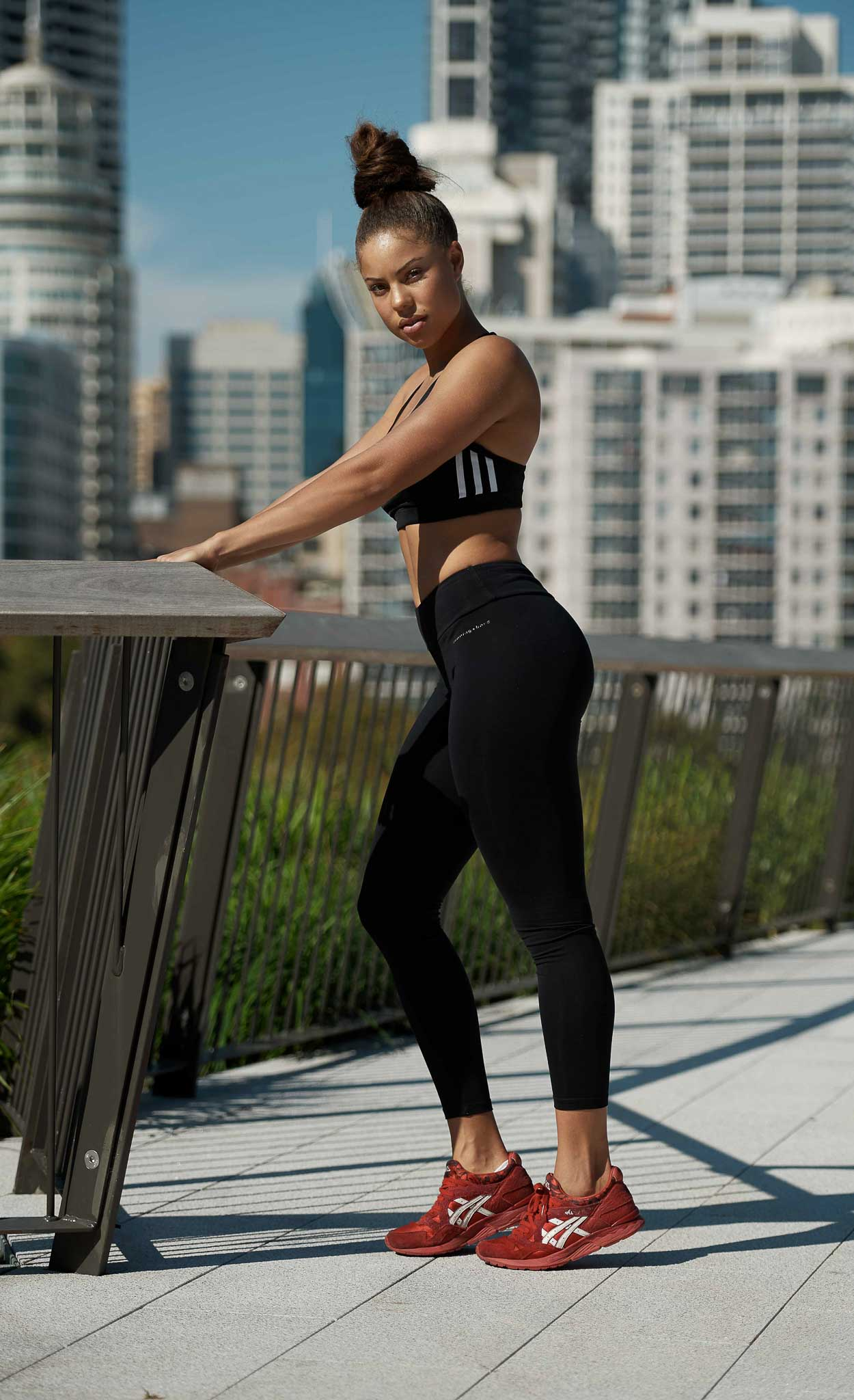 Kirsty looking fierce holding onto a rail wearing a black Adidas top and matching Adidas tight leggings