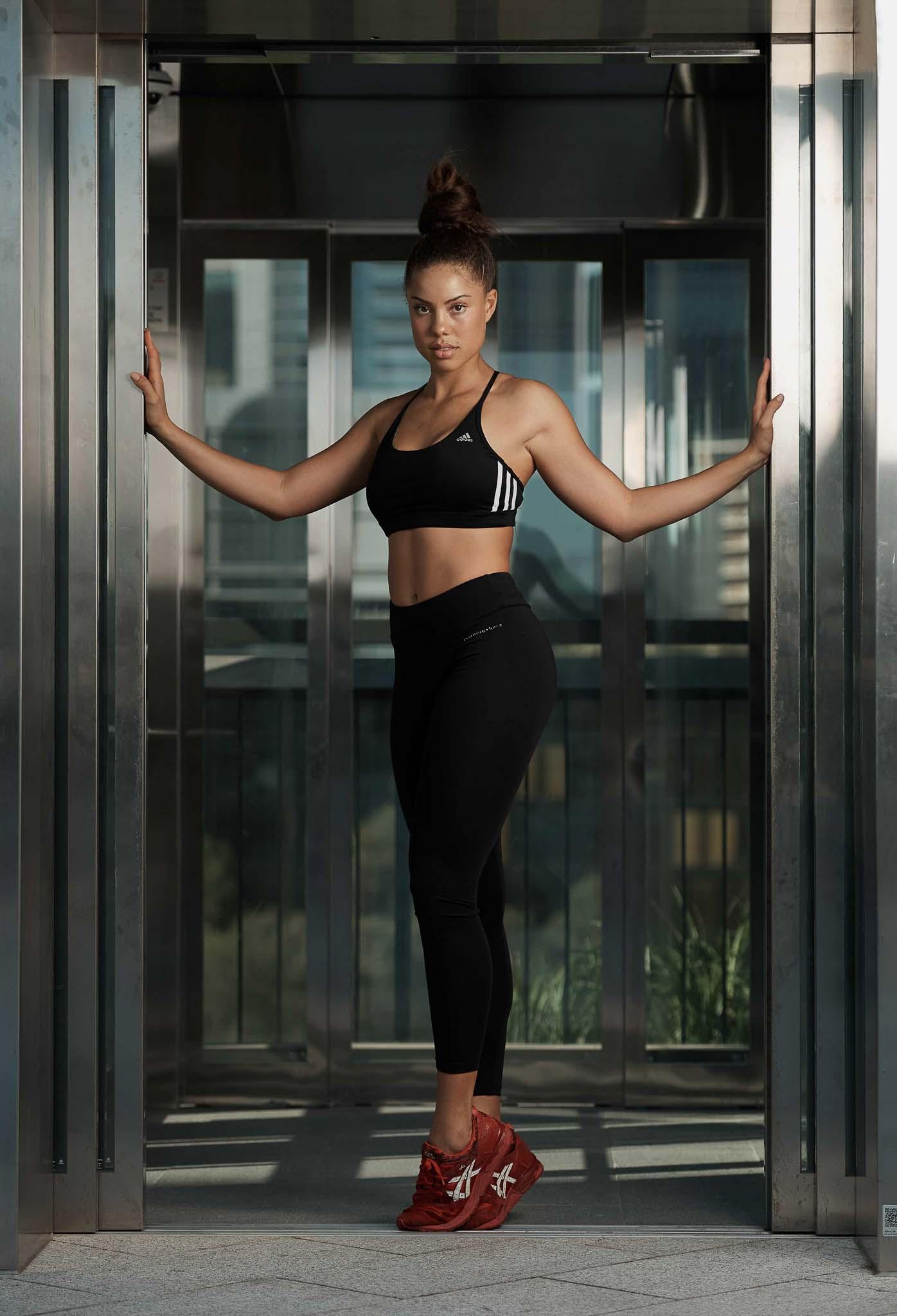 Kirsty standing in doorway wearing black Adidas leggings and Adidas crop top