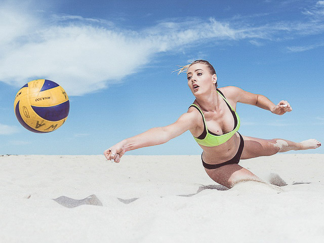Lauren diving in the sand as she hits beach volleyball