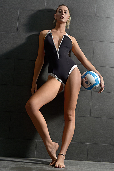 Lauren posing in full one piece black swimsuit with netball
