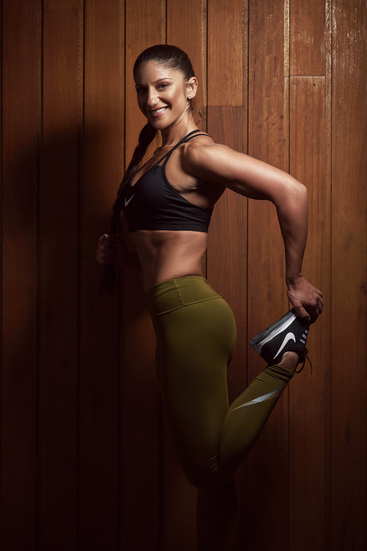 Layla stretching against timber wall with green Nike pants and black Nike runners