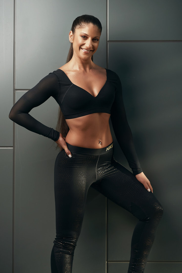 Layla wearing Nike shiny workout pants and black tight crop top with sleeves