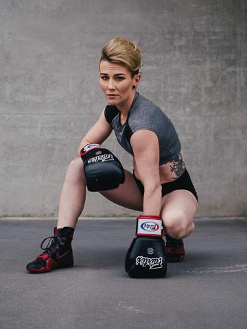 Lisa Brisbane's kickboxing champion kneeling