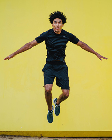 Luis jumping in a crucifix position against a yellow background