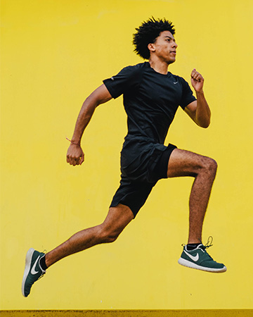 Luis running against a yellow background