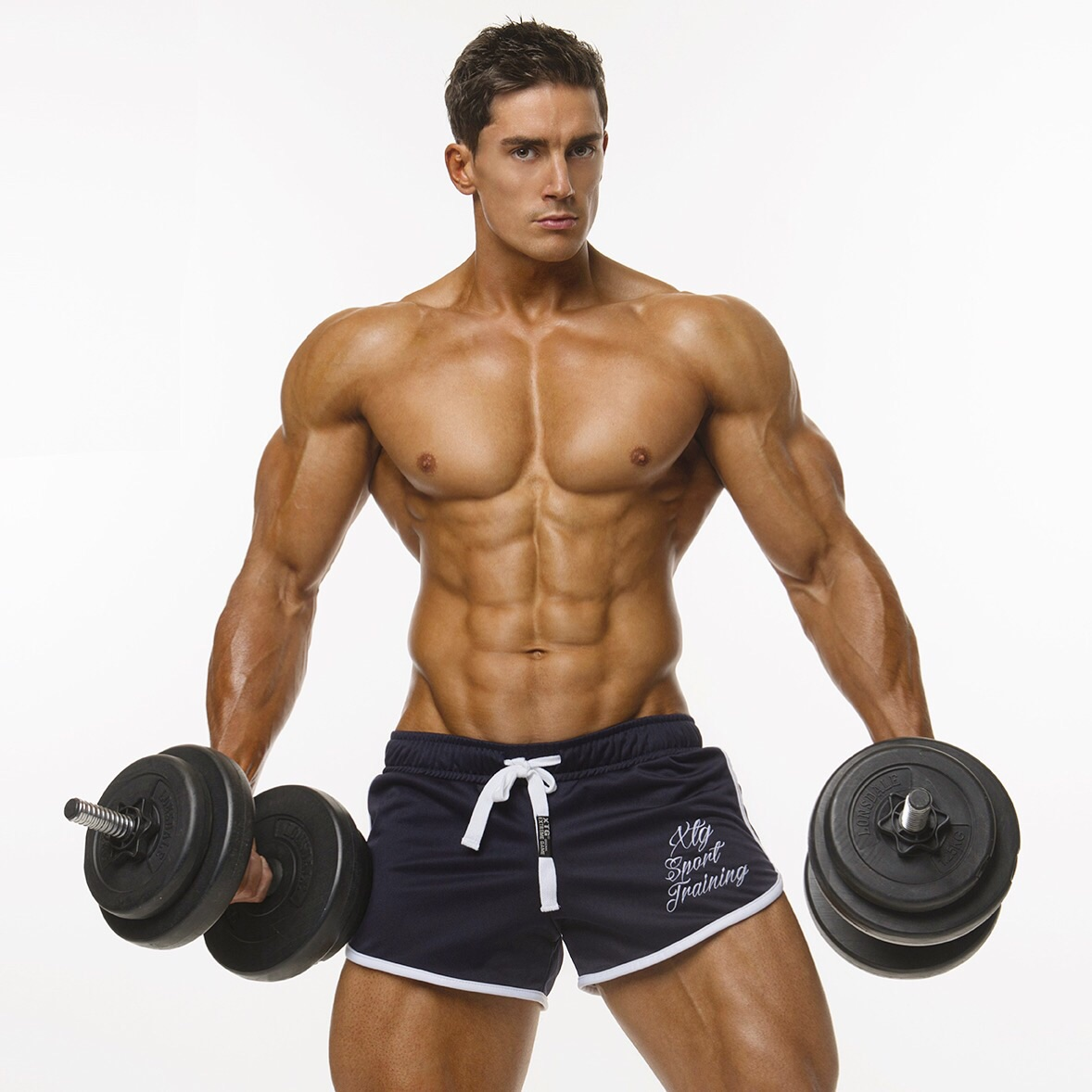 Martin S in studio holding two dumbbells and flexing upper body