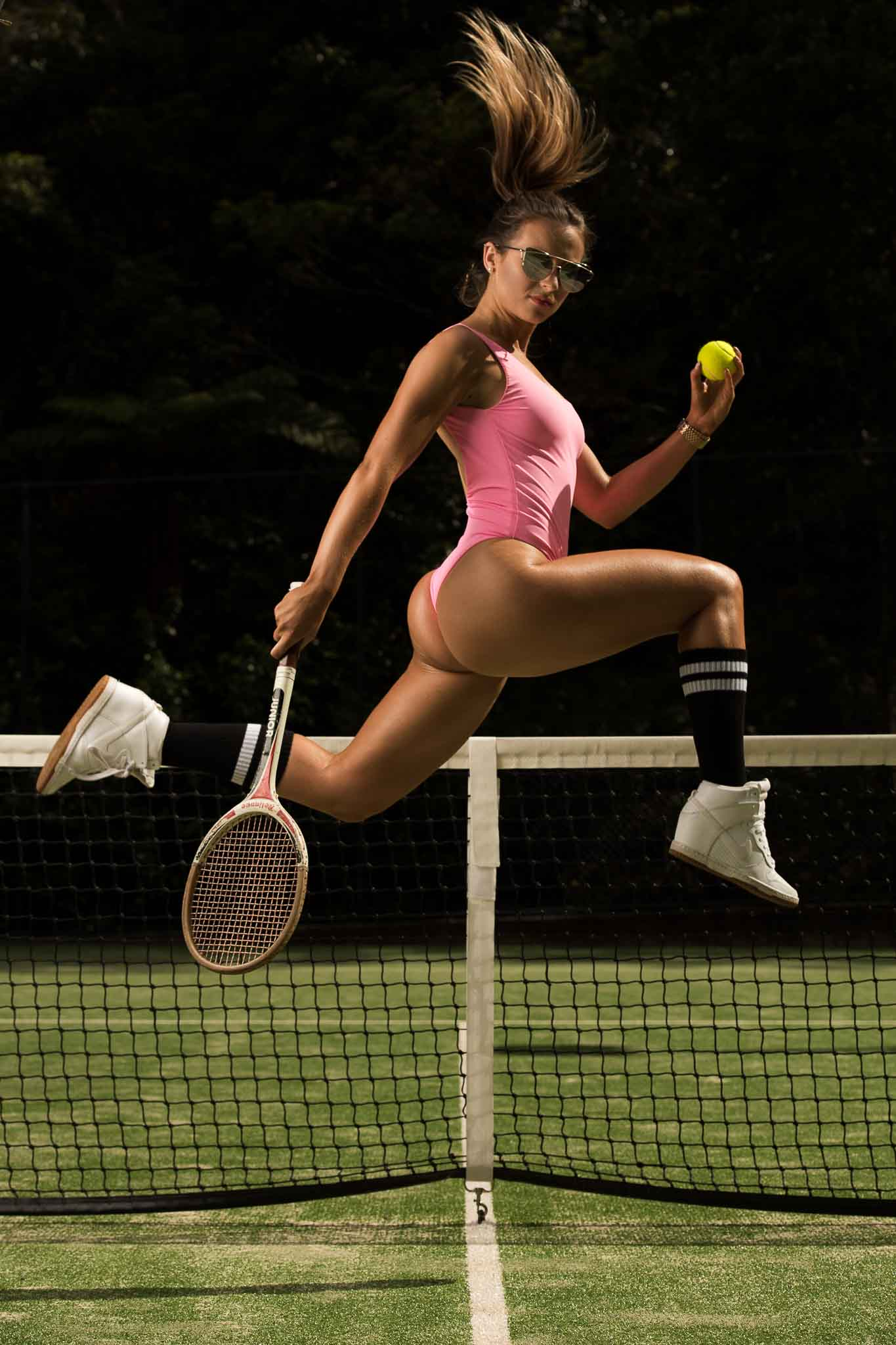 Maya Jumping on tennis court wearing high black socks and full one piece pink swimsuit