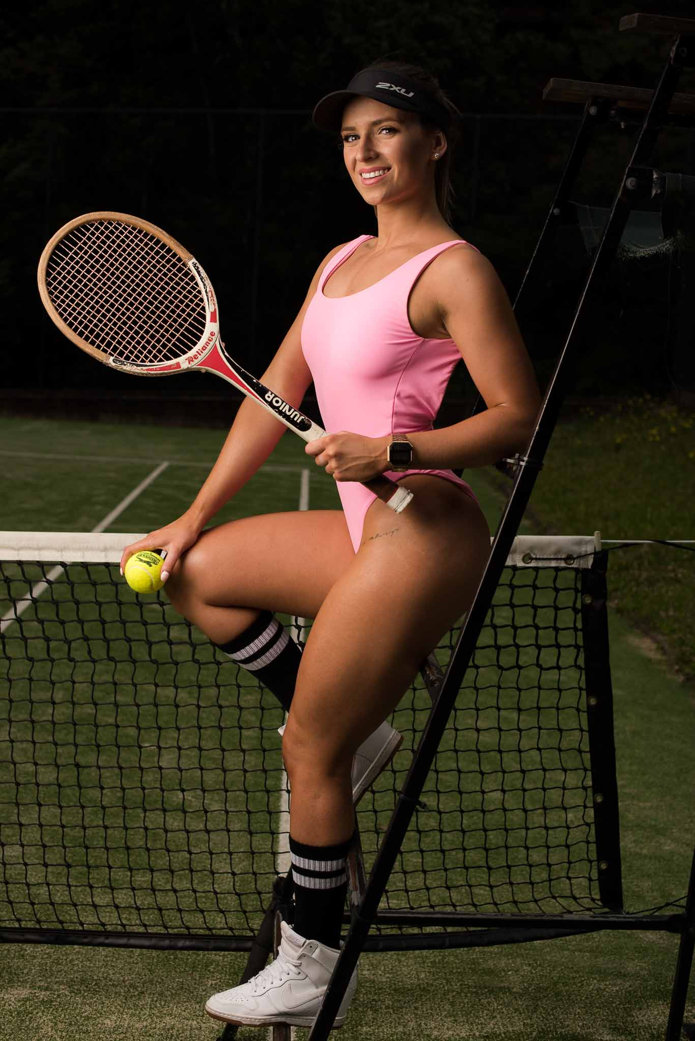 Maya Sitting on tennis nets holding tennis racket whilst wearing pink one piece swimsuit