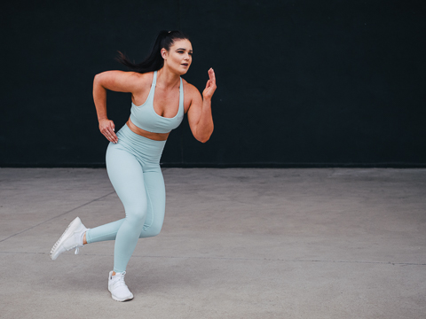 Megan jumping, sidestepping in turquoise leggins and matching top