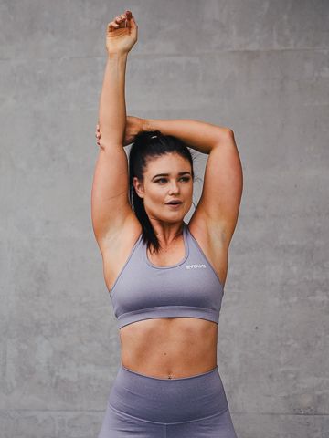 Megan performing an overhead tricep stretch