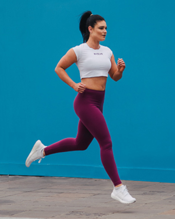 Megan running bounding against a blue wall wearing a white and red jog pants