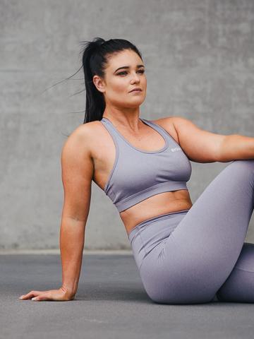 Megan seated on concrete floor against concrete backdrop