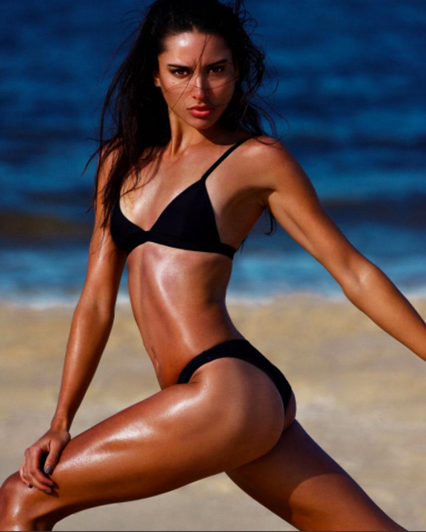 Montana lunging on the beach wearing black bikini bottoms and top
