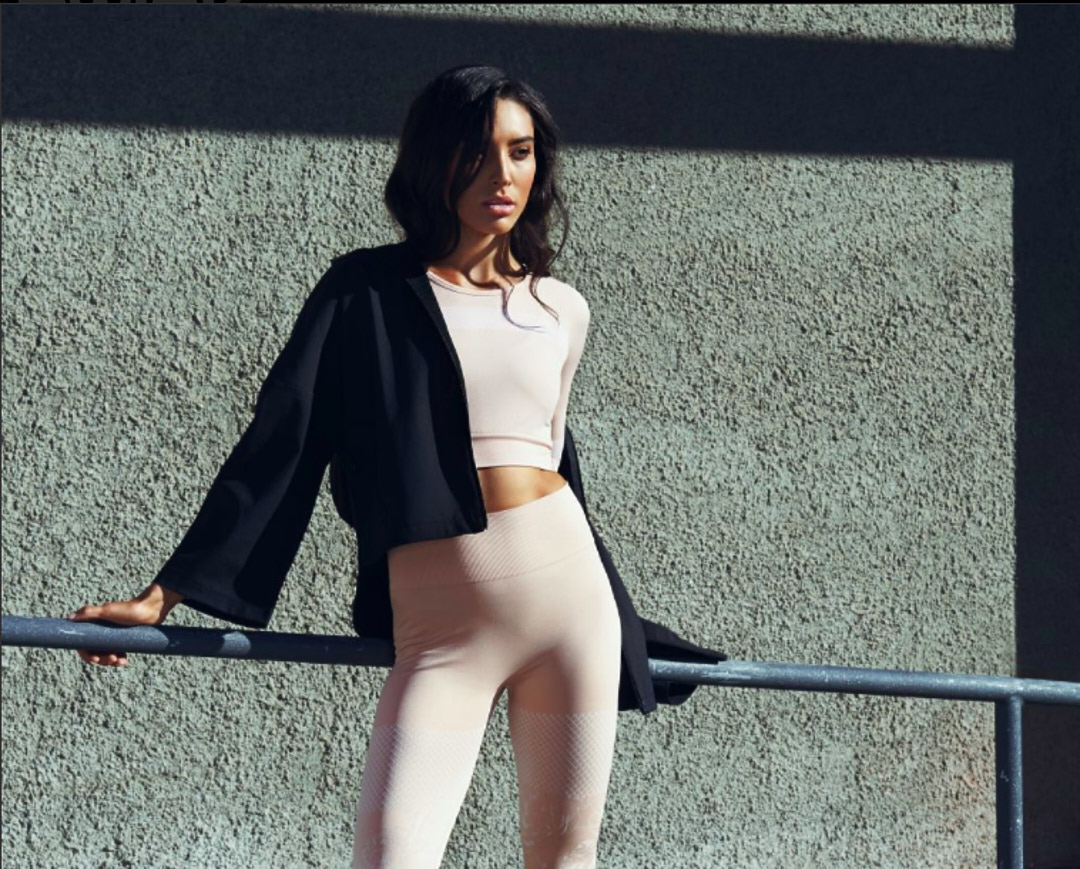 Montana standing, leaning against a metal rail wearing a tight fitted beige sports top and matching leggings with a black overcoat draped over her shoulders