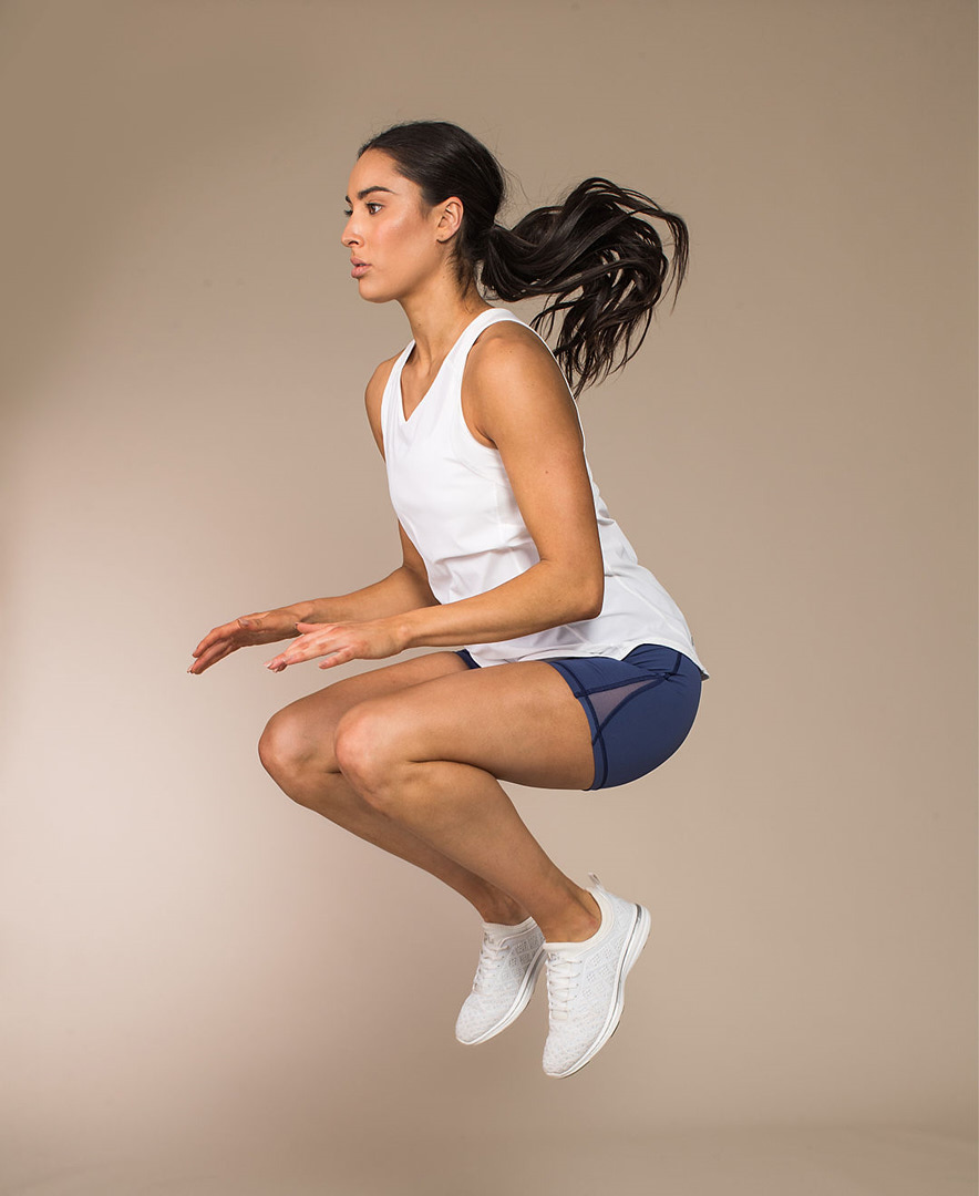 Montano jumping during Lululemon studio campaign wearing blue tight shorts and loose white fitness top