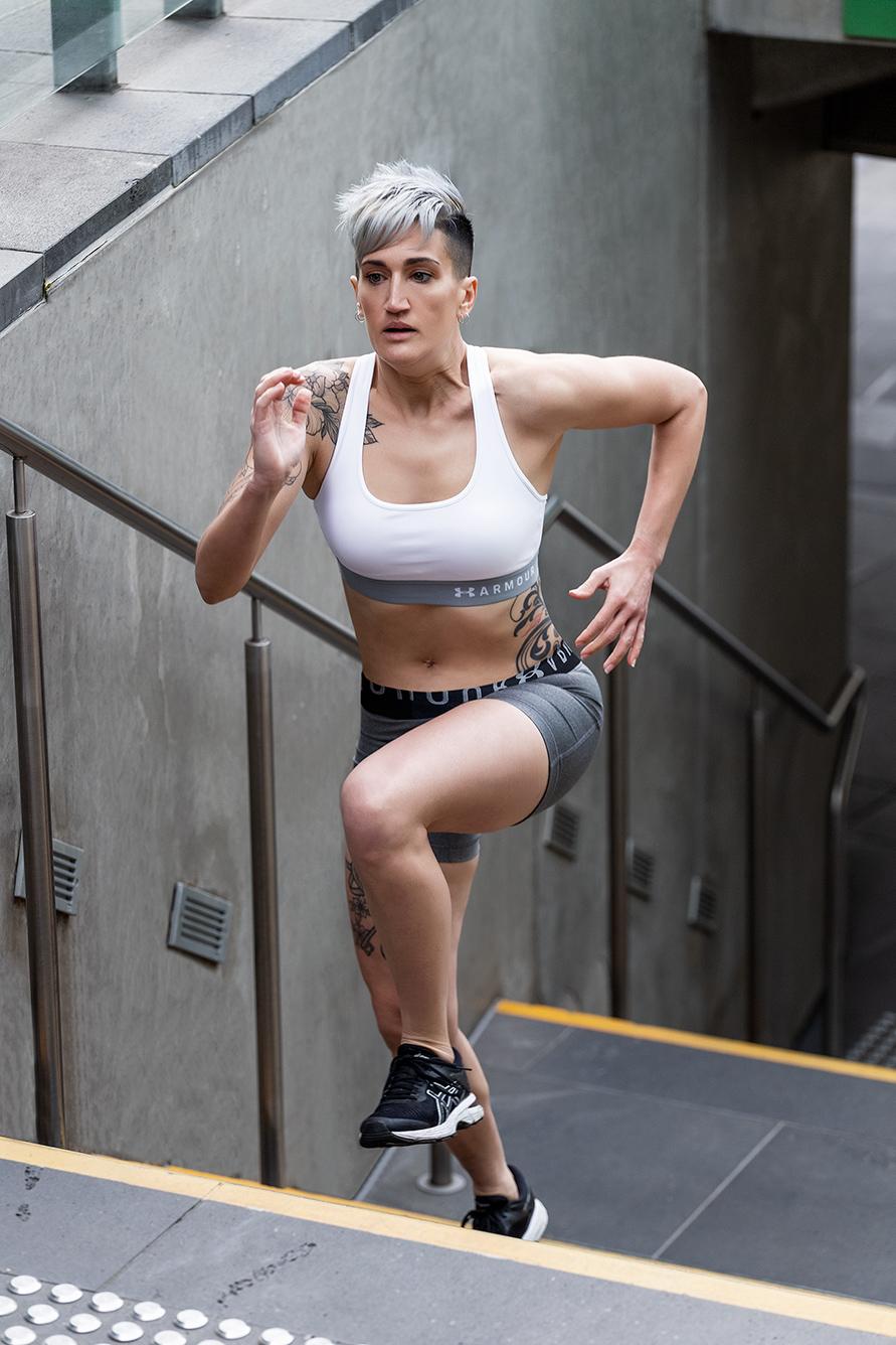 Natalie E australian kickboxing champion running up stairs