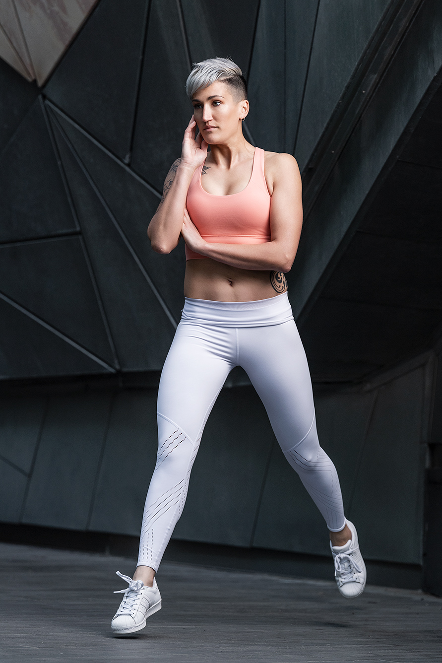 Natalie E striding, jogging in fitted white compression pants and peach exercise top