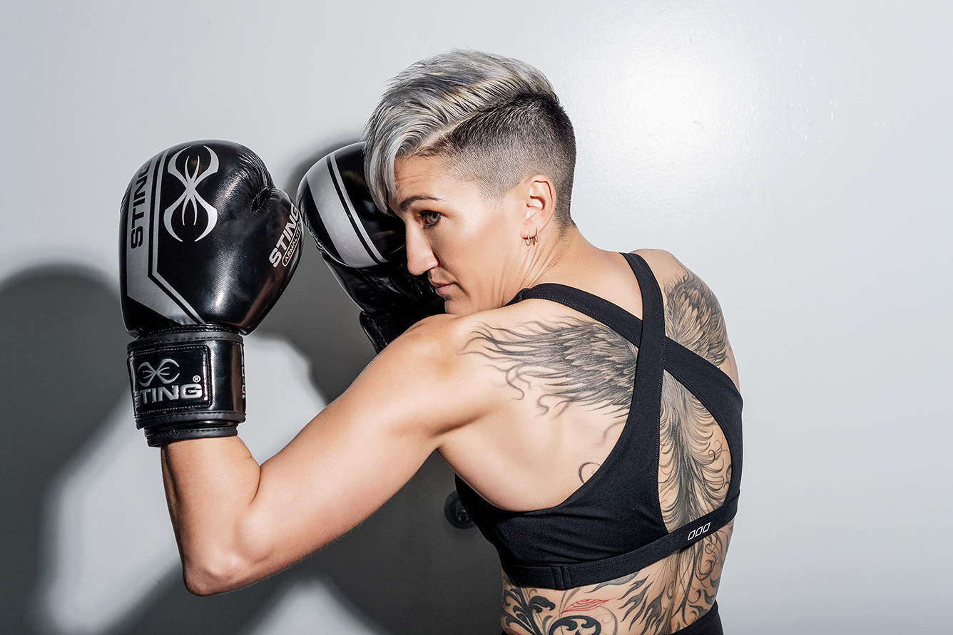 Natalie E throwing a left uppercut displaying her wonderful full back tattoo