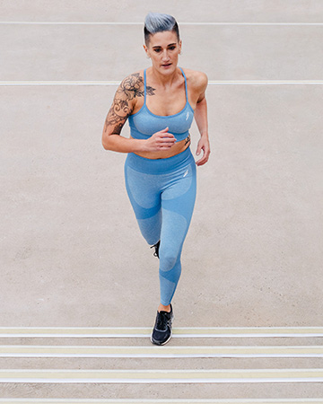 Natalie running up a flight of stairs in matching blue compression tights and blue crop top