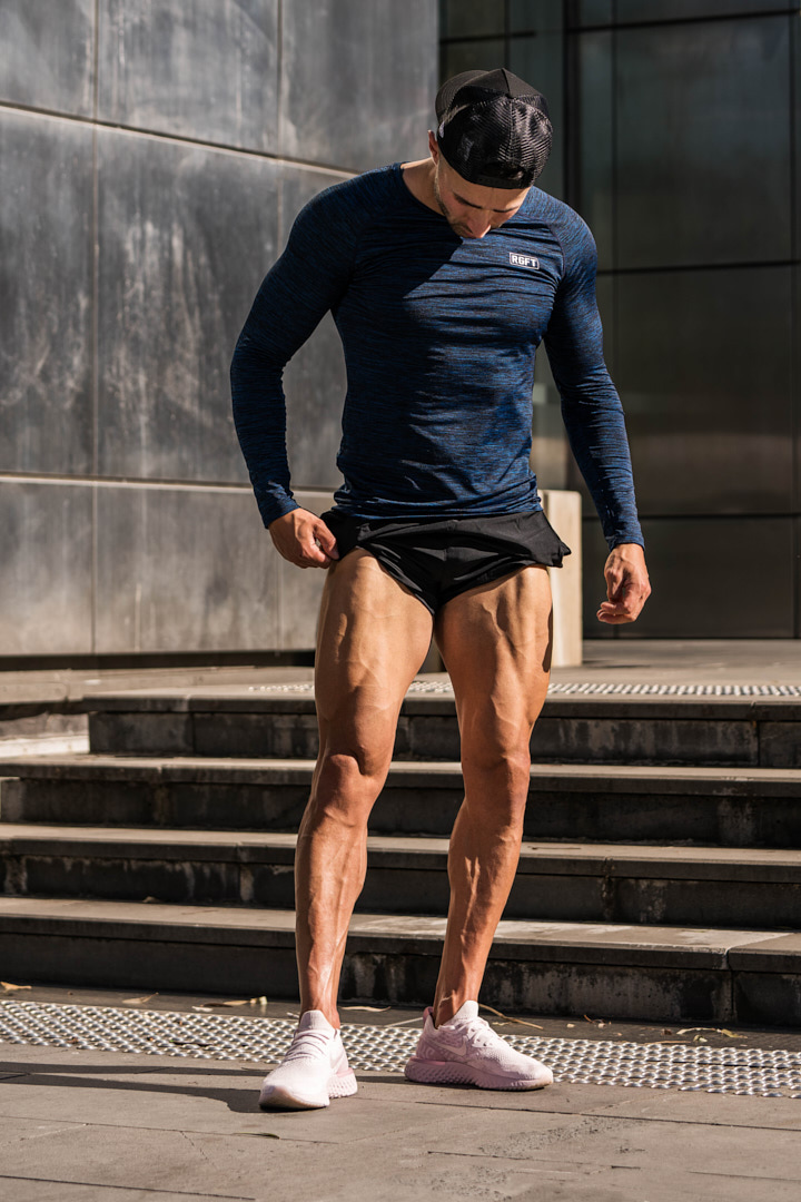 Nathan standing at the base of the stairs flexing his quads