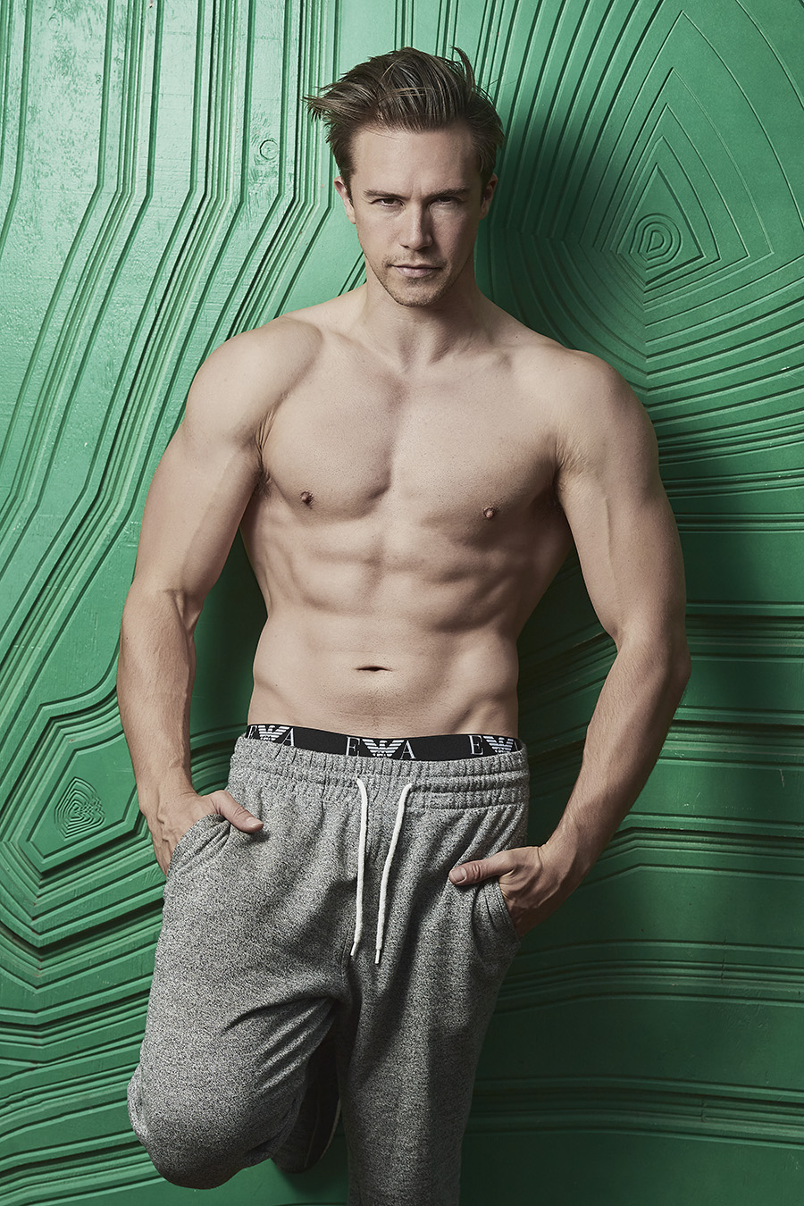 Neal English male fitness model wearing grey sports pants leaning against a green wall