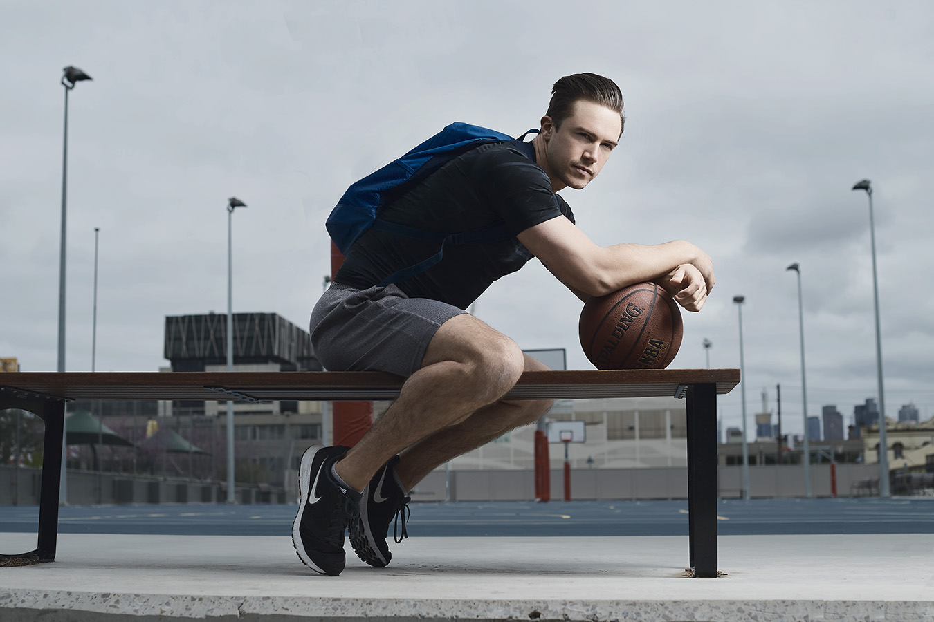 Neal Seated on a bench leaning against basketball