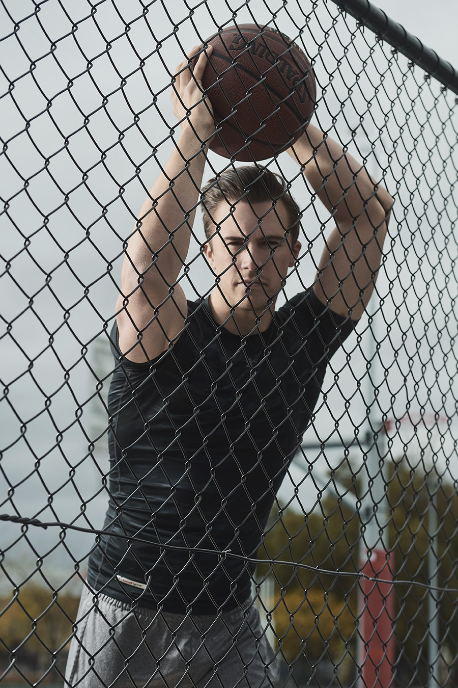 Neal holding basketball over his head behind wired fence