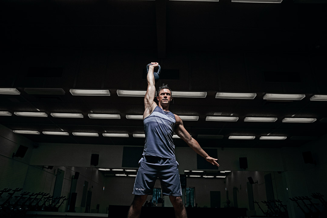 Neal performing a overhead squat with Kettlebell during bison fitness campaign