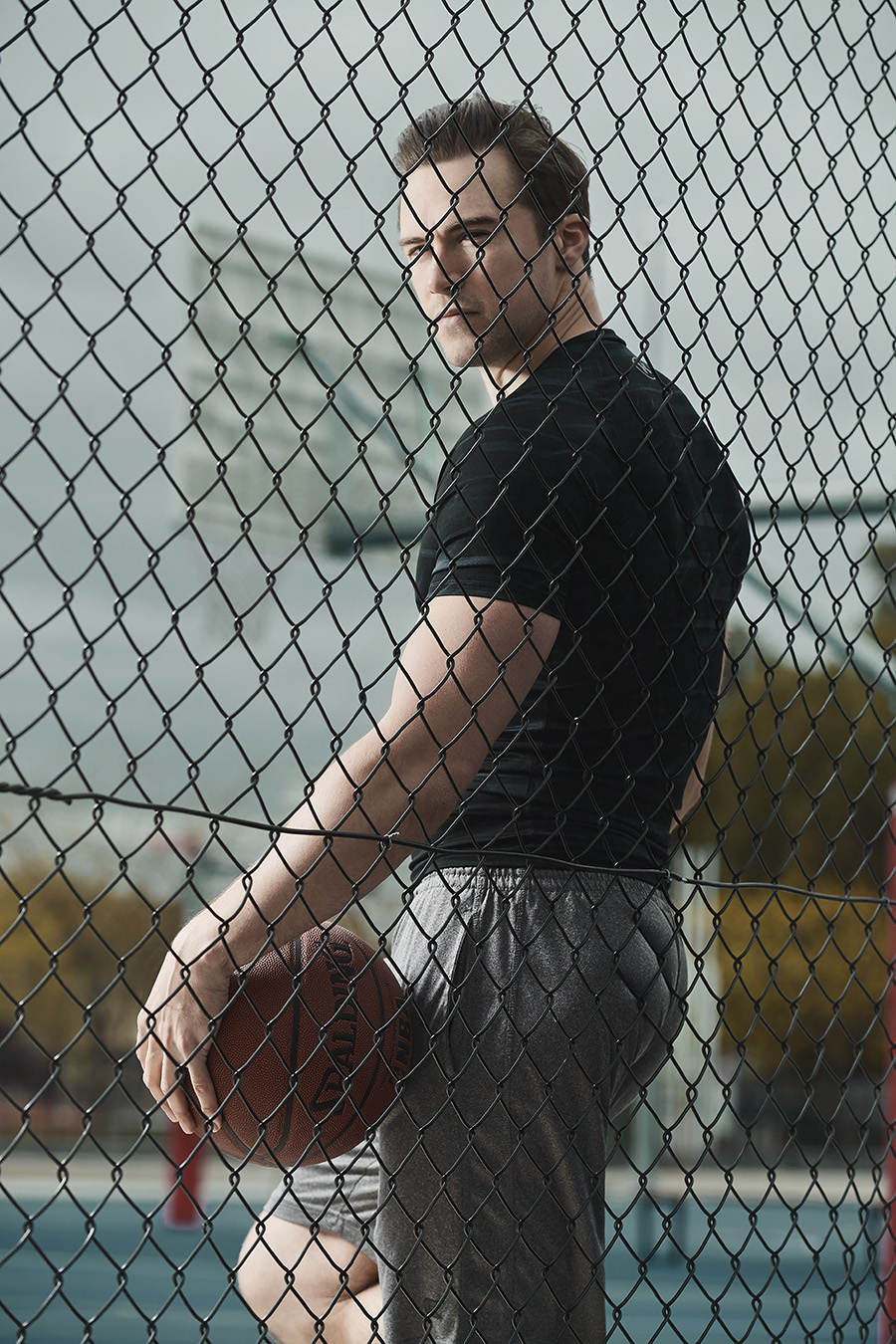 Neal standing behind wire fence on basketball court