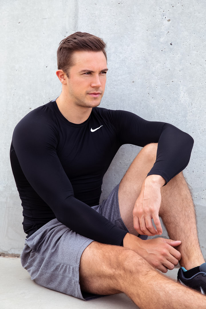 Neil seated against concrete wall wearing long sleeve compression gear