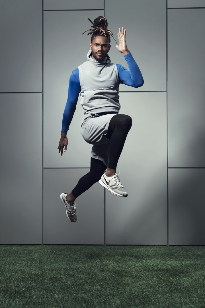 Nic jumping wearing skins grey Nike shorts and a tight blue fitted top