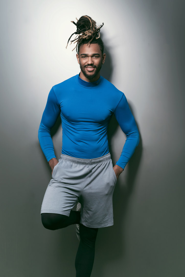 Nic leaning against a silver metallic wall wearing sport shorts and fitted blue exercise top