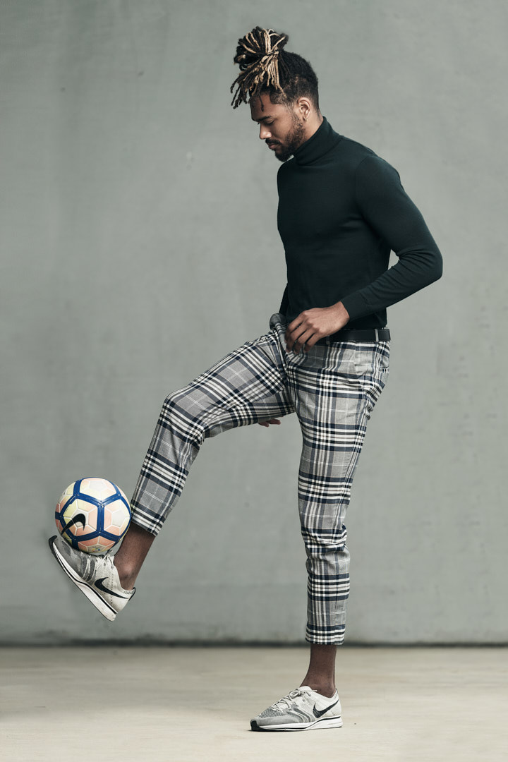 Nick performing soccer tricks whilst wearing patterned grey trousers and a green wall knitted top